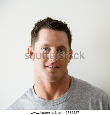 Head and shoulder portrait of man in t-shirt against white wall. - stock photo