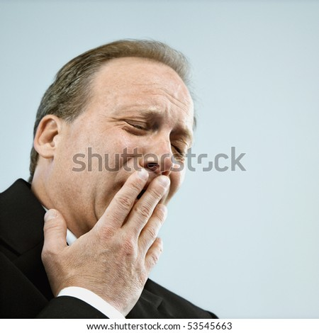 Head and shoulder portrait of middle aged  Caucasian businessman yawning. - stock photo