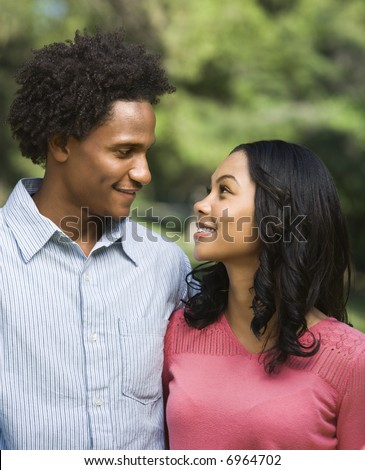 Head and shoulder portrait of smiling couple looking into eachother's eyes.
