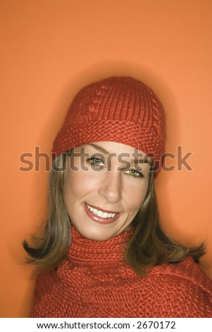 Head and shoulder portrait of smiling young adult Caucasian woman on orange background wearing winter hat and scarf.