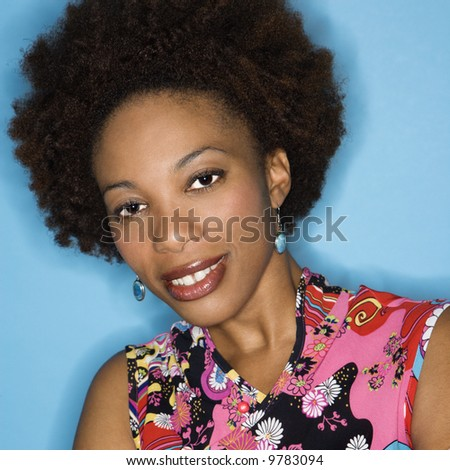 Head and shoulder portrait of woman with afro wearing vintage print fabric.