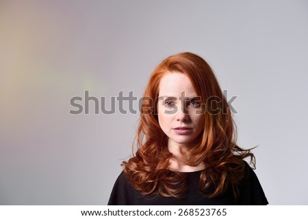 Head and Shoulder Shot of a Pretty Red Haired Young Woman in a Black Shirt Looking at the Camera, Isolated on Gray Background - stock photo