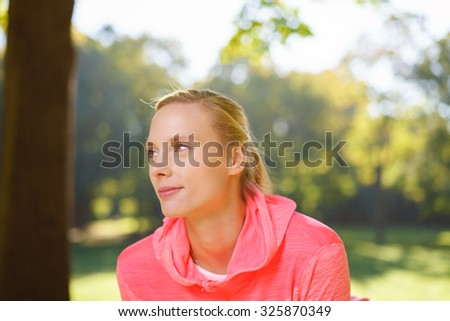 Head and Shoulder Shot of a Thoughtful Woman Looking Into the Distance with Half Smile Face Against a Tranquil Park Background at Early in the Morning - stock photo