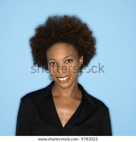 Head and shoulder studio portrait of smiling happy woman on blue background.