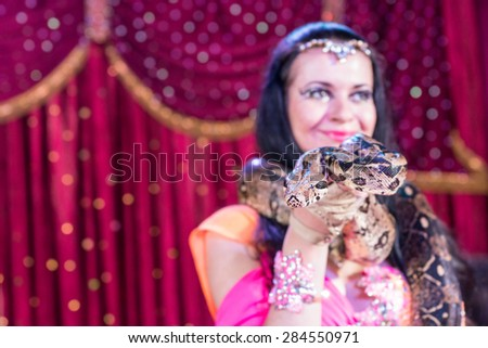 Head and Shoulders Close Up Portrait of Exotic Dark Haired Snake Charmer Wearing Large Snake Around Shoulders on Stage with Red Curtain - Focus on Face of Snake with Copy Space - stock photo