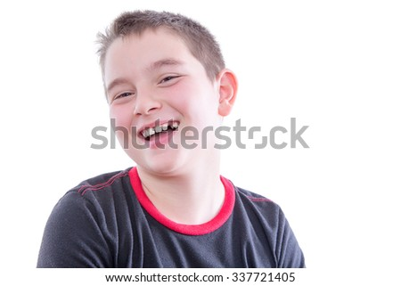 Head and Shoulders Close Up Portrait of Young Boy Wearing Black and Red Shirt Laughing and Showing Braces in Bright Studio with White Background and Copy Space - stock photo