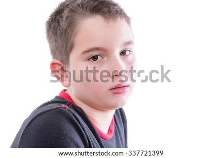 Head and Shoulders Close Up Portrait of Young Boy Wearing Black and Red Shirt Staring Blankly at Camera in Studio with White Background and Copy Space - stock photo