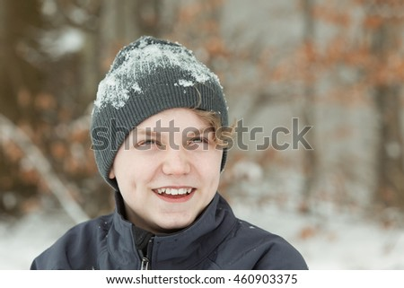 Head and Shoulders Close Up Portrait of Young Teenage Boy Outside in Winter Wearing Jacket and Gray Knitted Hat Caked in Snow, Smiling on Winter Day with Copy Space