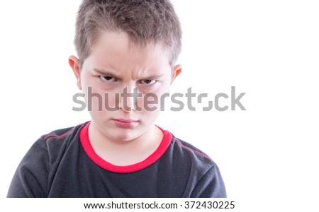 Head and Shoulders Close Up Portrait of Young Tween Boy Wearing Black and Red T-Shirt Frowning with Furrowed Brow at Camera in Studio with White Background and Copy Space - stock photo
