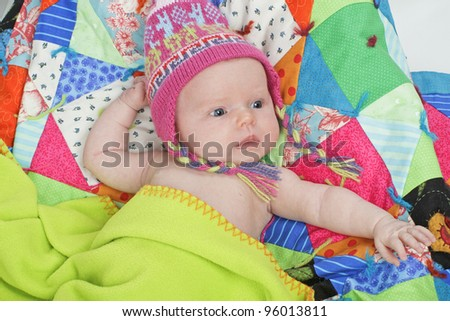 Head and shoulders fashion portrait of infant wearing a Peruvian knit hat. Colorful patchwork quilt background, horizontal layout. - stock photo