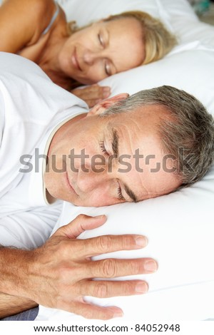 Head and shoulders mid age couple sleeping - stock photo