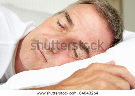 Head and shoulders mid age man sleeping - stock photo