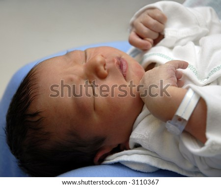 Head and shoulders of a sleeping day-old infant, hospital bracelet still on. - stock photo