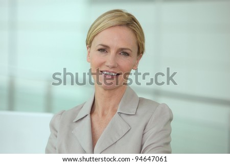 Head and shoulders of a smiling businesswoman in a biege suit - stock photo