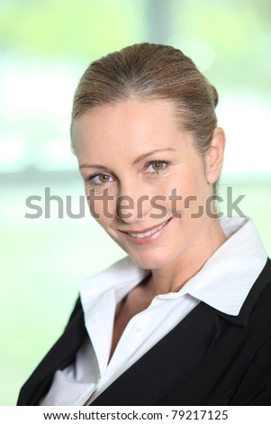 Head and shoulders of a smiling female executive - stock photo