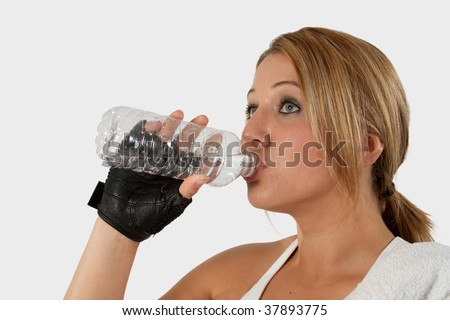 Head and shoulders of an attractive young blond woman in workout attire holding and drinking from a water bottle with a glove on hand - stock photo