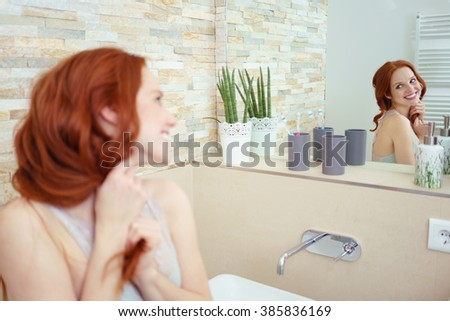 Head and Shoulders of Attractive Young Woman with Red Hair Smiling and Admiring Reflection in Mirror in Luxury Bathroom - stock photo