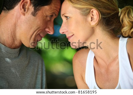 Head and shoulders of mature romantic couple looking at each other - stock photo