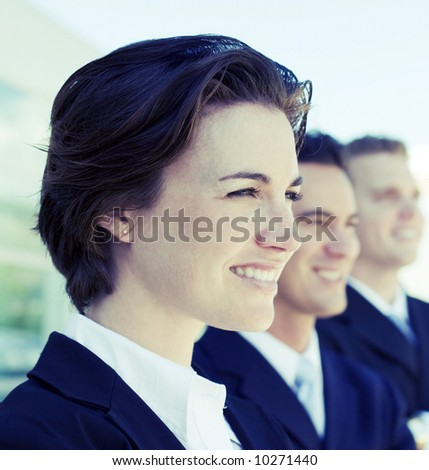 head and shoulders of three business people looking in same direction smiling - stock photo