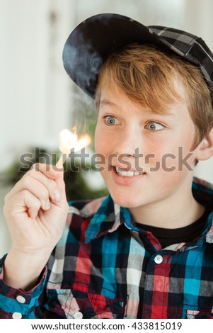 Head and Shoulders of Young Teenage Boy Wearing Baseball Cap and Plaid Shirt Looking Mesmerized by Flame of Lit Match - stock photo