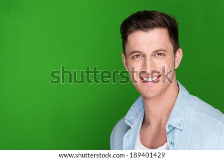 Head and shoulders portrait against a green background with copyspace of a handsome friendly young man looking at the camera with a warm sincere smile - stock photo
