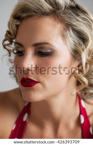 Head and shoulders portrait of a beautiful mid 30s woman dressed in vintage retro polka dot bikini looking away