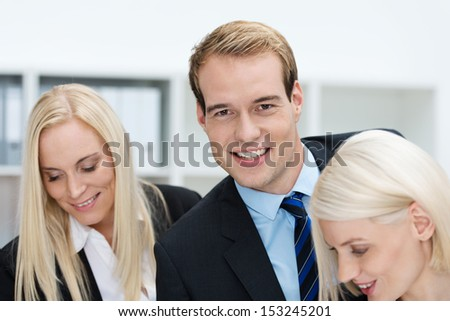 Head and shoulders portrait of a charming handsome young businessman working in the office with two attractive female colleagues - stock photo