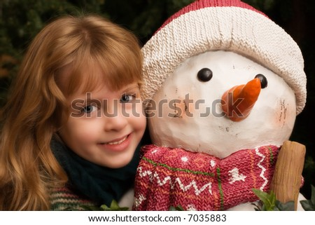 Head and shoulders portrait of a cute little girl hugging a snowman.