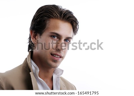Head and shoulders portrait of a handsome fashionable young man in an open necked shirt and light brown jacket looking at the camera with a serious expression, isolated on white with copyspace