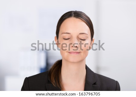 Head and shoulders portrait of a serene young professional woman standing meditating or thinking deeply with her eyes closed - stock photo