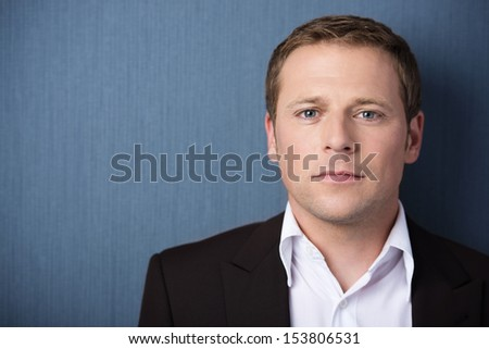 Head and shoulders portrait of a serious concerned businessman looking directly at the camera with a steady gaze against green with copyspace - stock photo