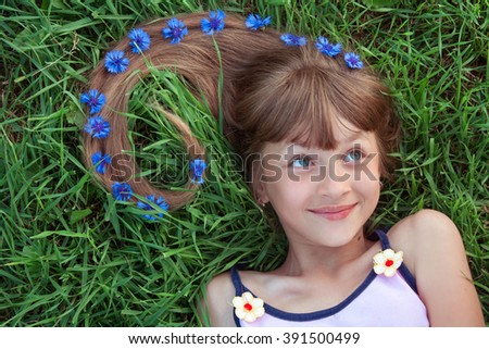 Head and shoulders portrait of a smiling girl with cornflowers in her long hair lying on the grass and looking right - stock photo