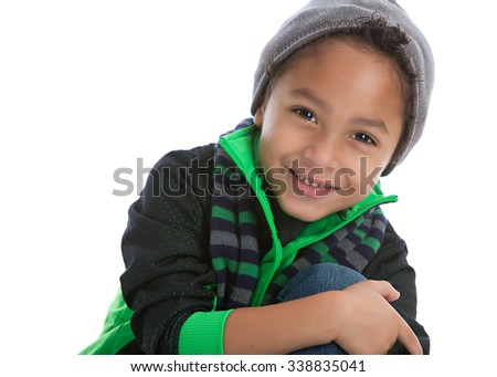Head and shoulders portrait of a young mixed race boy wearing a jacket, scarf and knit hat.  Isolated on white with room for your text. - stock photo