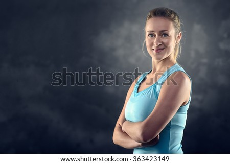 Head and Shoulders Portrait of an Athletic Blond Woman Wearing turquoise Tank Top and Standing with crossed arms in Studio with Grey Background