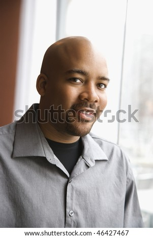 Head and shoulders portrait of an attractive African-American man smiling near a window. Vertical shot. - stock photo
