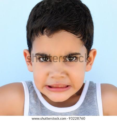 Head and shoulders portrait of avery upset hispanic boy - stock photo