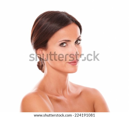 Head and shoulders portrait of beautiful sensual adult female wondering while looking at camera with nude shoulders on isolated studio - stock photo