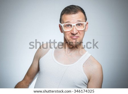 Head and shoulders portrait of funny young man. Close-up crazy guy in undershirt over gray background - stock photo