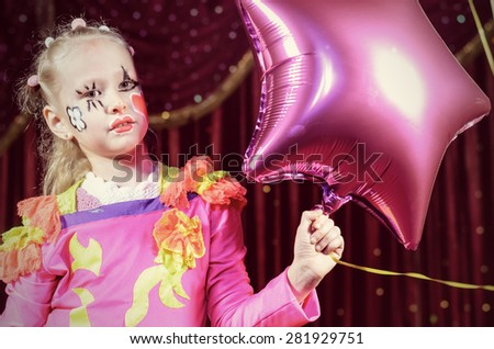 Head and Shoulders Portrait of Young Blond Girl Wearing Clown Make Up and Costume Holding Star Shaped Balloon on Stage in front of Red Curtain - stock photo