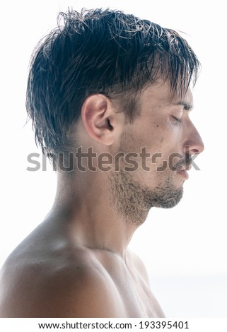 Head and shoulders profile portrait of a tousled unshaven shirtless young man with closed eyes and a serious expression isolated on white - stock photo