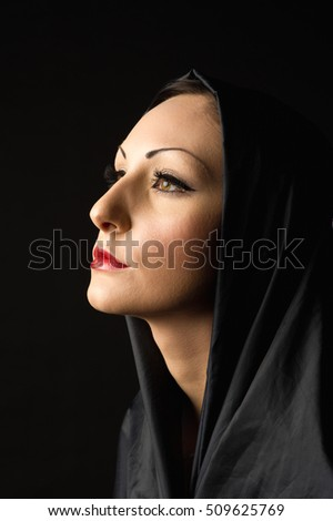 head and shoulders shot of a beautiful woman on a black background with a black vail and golden brown eyes