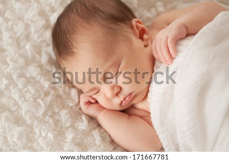 Head and shoulders shot of a sleeping two week old newborn baby wrapped in white gauzy fabric and sleeping on a white billowy blanket.