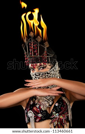 Head and Shoulders shot of an exotic belly dancer wearing a red and black costume with hijab and fire headdress. Shot in the studio on an isolated black background. - stock photo
