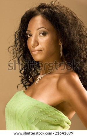 Head and shoulders shot of beautiful middle aged woman with long hair wearing green tube top or piece of cloth