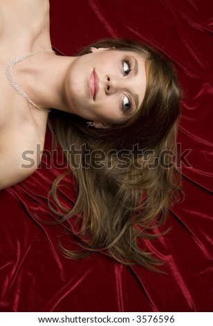 head and shoulders shot of brunette girl on red fabric. shot from above.
