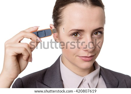 Head and shoulders studio shot of a pretty business model holding a usb memory stick to the side of her head  - stock photo