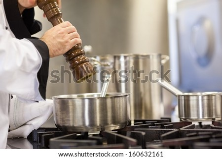 Head chef flavoring food with pepper in professional kitchen - stock photo