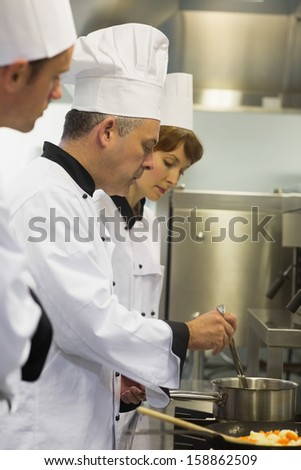 Head chef inspecting his students pot in a kitchen - stock photo