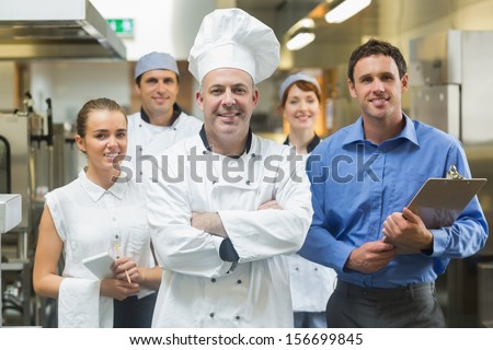 Head chef posing with the team behind him in a profesionnal kitchen - stock photo