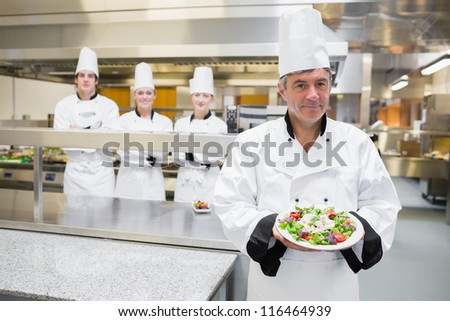 Head chef presenting salad with his team standing behind him - stock photo